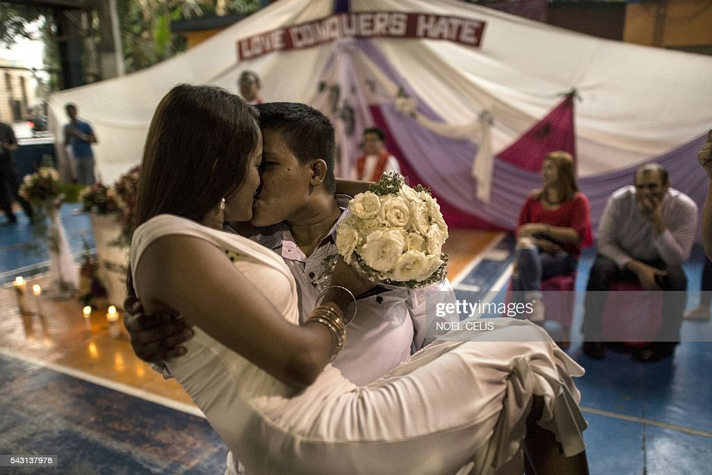 A couple kisses as members of the lesbian, gay, bisexual and transgender (LGBT) community take part in a 'Rite of Holy Union' ceremony in Manila on June 26, 2016, that coincided with Gay Pride celebrations the day before. The Philippines has a vibrant gay scene despite a macho culture and opposition from the Roman Catholic Church, but there are no anti-discrimination laws in the country and same-sex relationships are not officially recognised. / AFP / NOEL