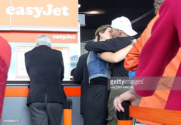 A couple kisses as they wait at a boarding counter on May 9 2010 at the Nice international airport French Riviera three days after the resumption of...
