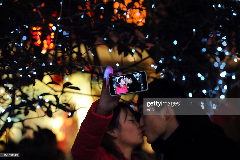 A couple kisses beside a Christmas decoration on Christmas Eve December 24, 2012 in Hefei, China. Though Christmas is not officially celebrated in China, the holiday is becoming increasingly popular as Chinese adopt more Western ideas and festivals.