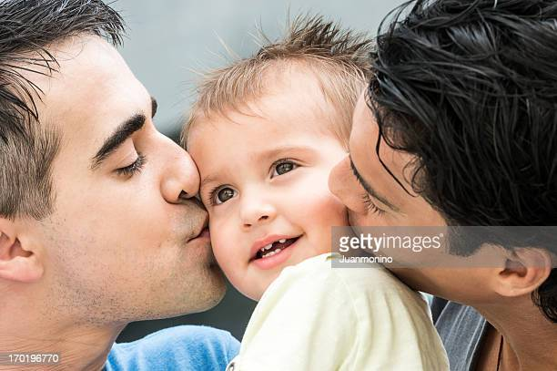 couple kisses each cheek of their child