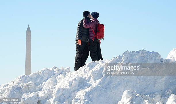 A couple kisses each other on top of a pile of snow in Washington on January 24 2016 Millions of people in the eastern United States started digging...
