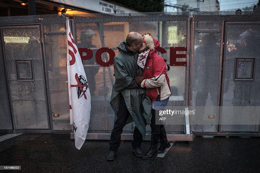 A couple kisses in front of riot police during a demonstration against the new LGV Lyon-Turin project, on December 3, 2012 in Lyon, on the sideline of the 30th France-Italy annual summit.