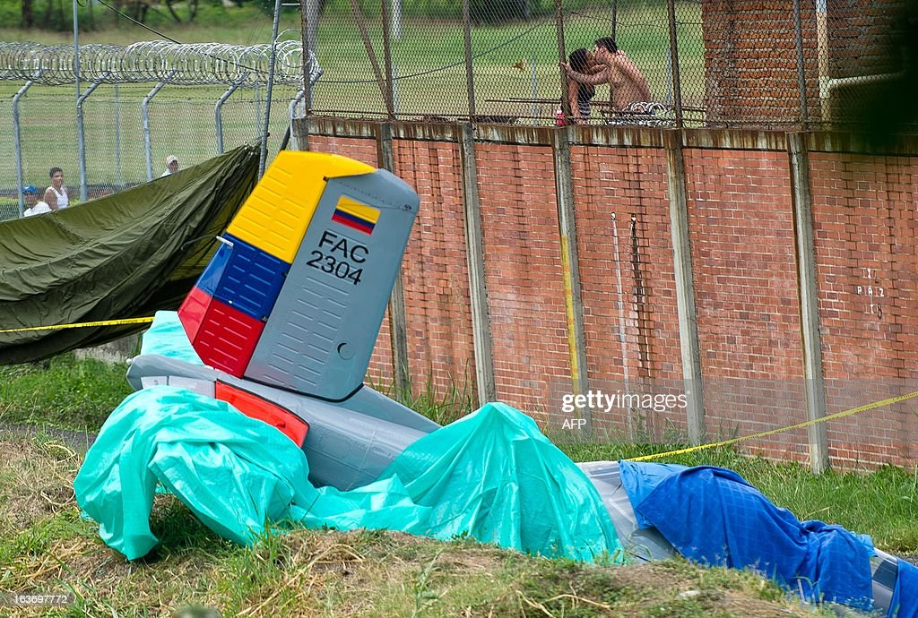 A couple kisses near the training airplane type T-34 of the Air Force of Colombia which crashed at the Military Aviation School 'Marco Fidel Suarez' on the outskirts of Cali, Valle del Cauca department, Colombia, on March 14, 2013. Colombian Air Force instructor, Lt. Col. Ricardo Cortes, and his student pilot Sublieutenant Juan Camilo Lancheros died in the accident.