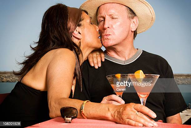 Couple Kissing and Drinking Cocktails by Sea