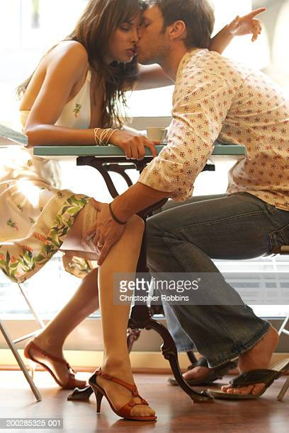 Couple kissing at cafe table, man holding woman's leg