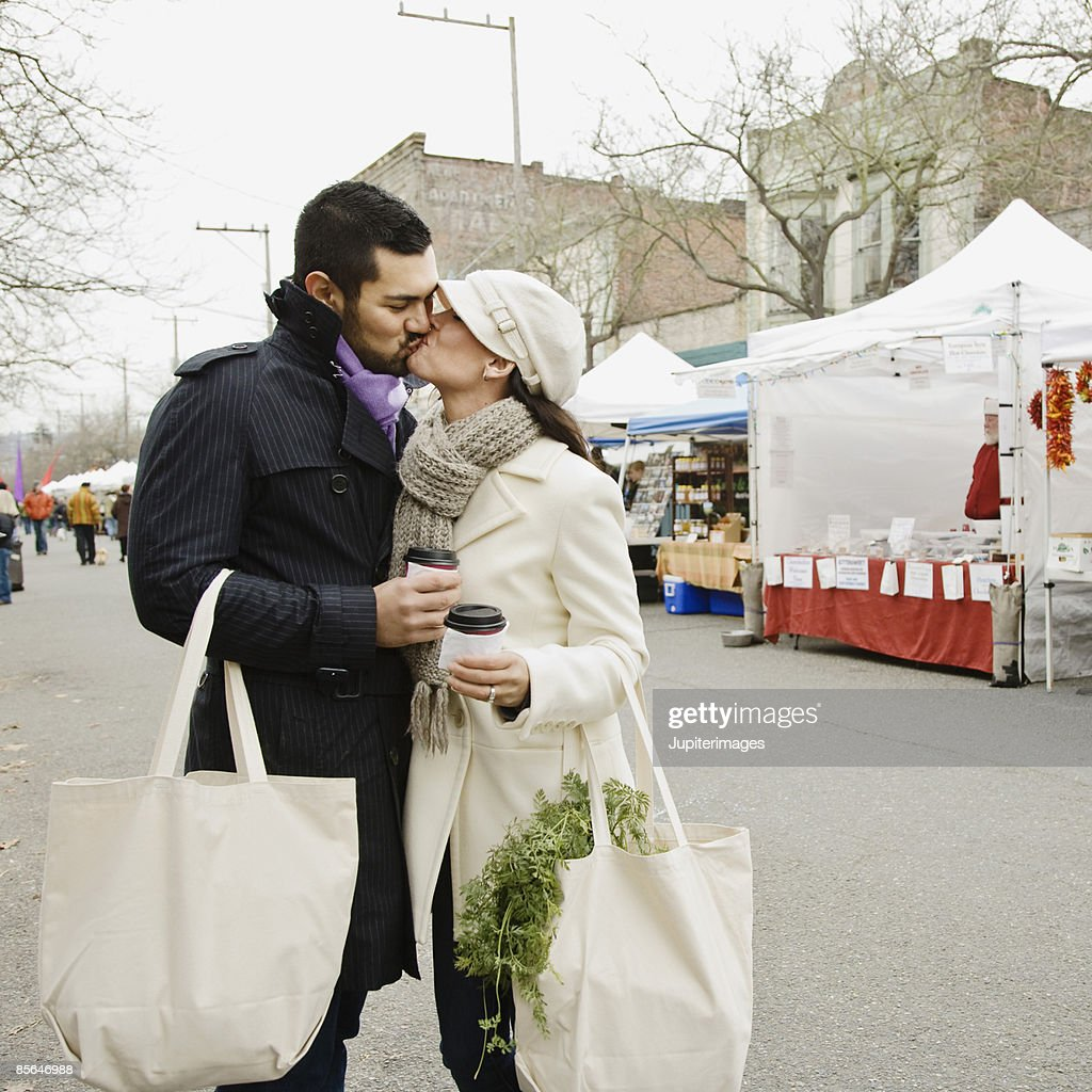 Couple kissing at farmer's market : Stock Photo