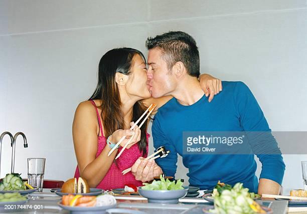 Couple kissing at sushi bar