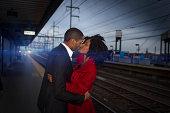 Couple kissing at train station