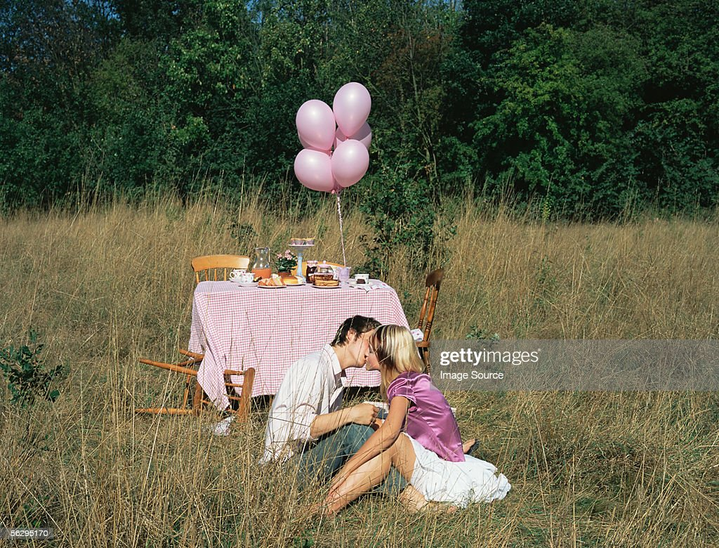 Couple kissing by a table in a field : Stock Photo