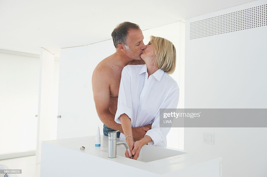 couple kissing by bathroom sink stock photo