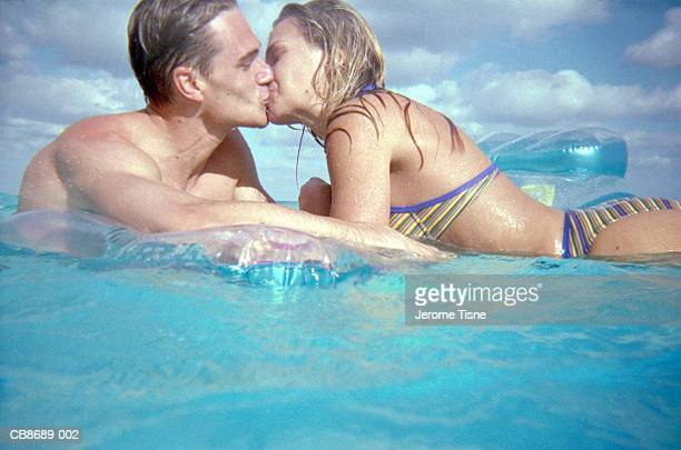 Couple kissing, floating on air bed in the sea.