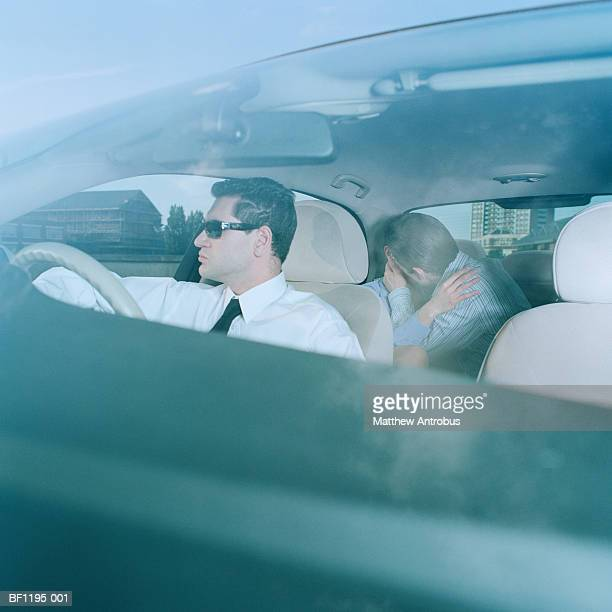 Couple kissing in back seat of chauffeur driven car