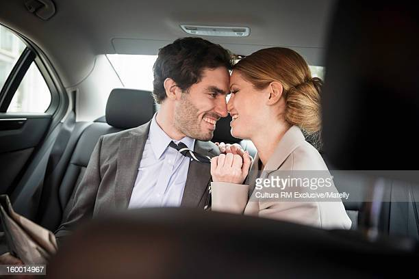 Couple kissing in backseat of car