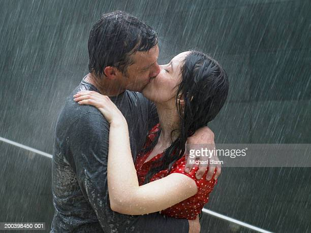 Couple kissing in rain, side view, close-up