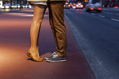 Couple kissing on Potsdamer Platz Berlin. The woman is standing on her tippy toes reaching up to kiss her boyfriend. Shot is from the waist down. Attractive young couple embracing on  Potsdamer Platz