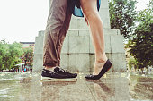 Legs of a man and a woman kissing under pouring rain