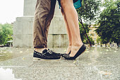 Ground view of young couple kissing in the rain