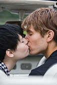 Couple kissing inside car