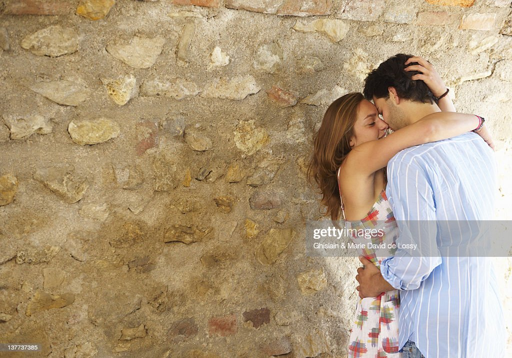 Couple kissing near stone wall : Stock Photo