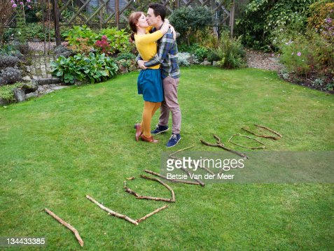 couple kissing next to handmade I love you sign. : Stock Photo