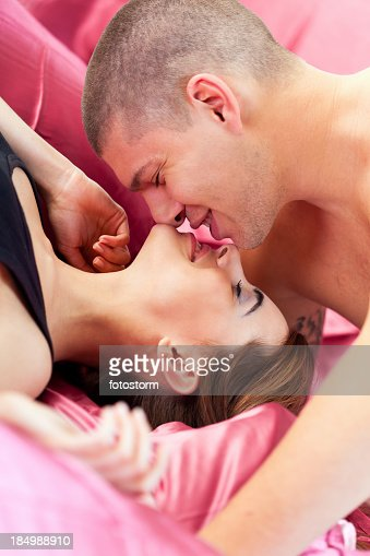 Couple kissing on pink bedsheets : Stock Photo