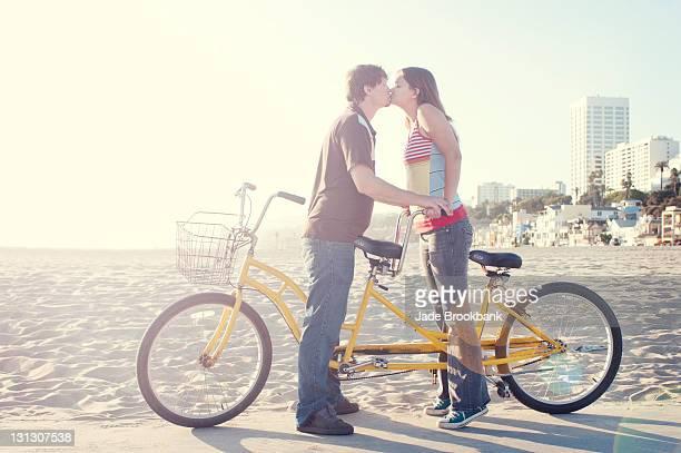Couple kissing on tandem bike on beach boardwalk