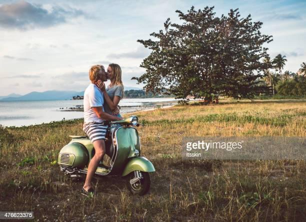 Coppia Baciarsi sulla spiaggia con scooter vintage