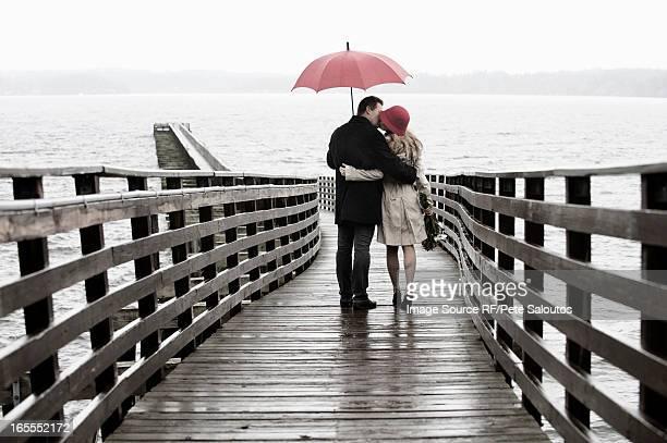 Couple kissing on wooden pier in rain