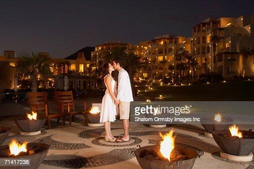 Couple kissing outdoors at resort hotel at night : Stock Photo