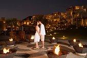 Couple kissing outdoors at resort hotel at night