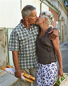 Couple kissing outdoors, man holding baguettes