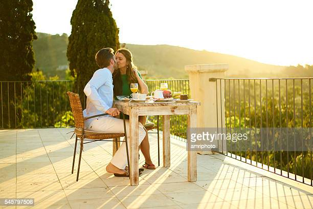 couple kissing outside at breakfast table