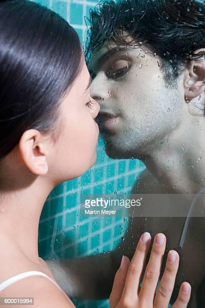 Couple Kissing Through Pane of Shower