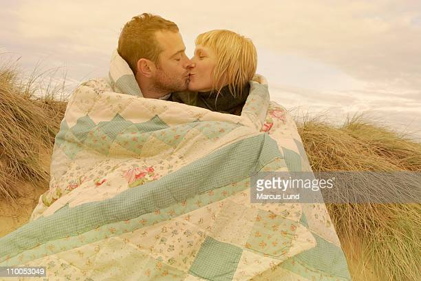 Couple kissing under blanket on beach