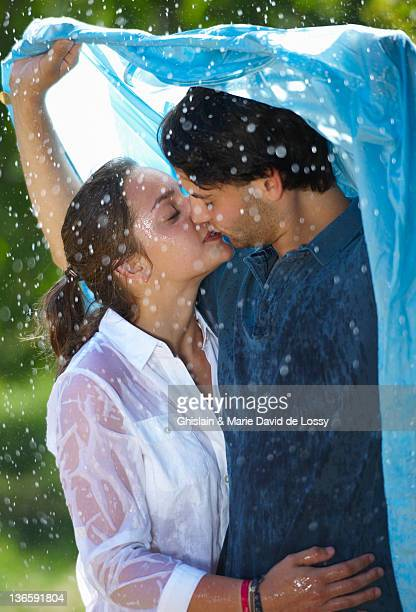 Couple kissing under cover in rain