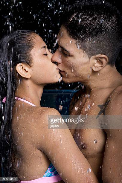 Couple kissing under watherfall in pool in Hawaii