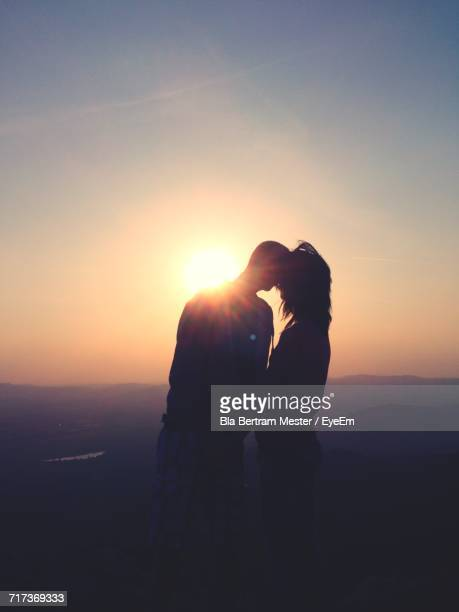 Couple Kissing While Standing On Cliff Against Clear Sky During Sunset
