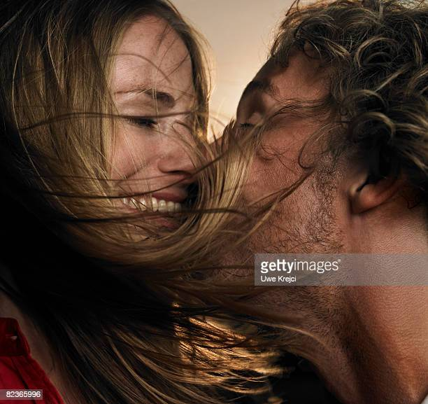 Couple kissing with hair blow in wind, close up
