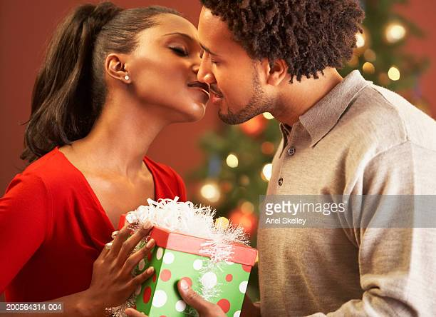 Couple kissing with holding Christmas gift, side view