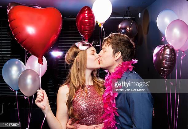 Couple kissing, woman holding heartshaped balloon.