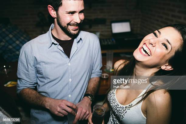 Couple laughing and drinking in nightclub