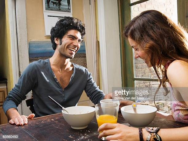 Couple laughing at breakfast table.