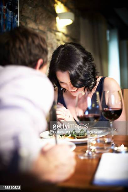 Couple laughing at dinner in restaurant