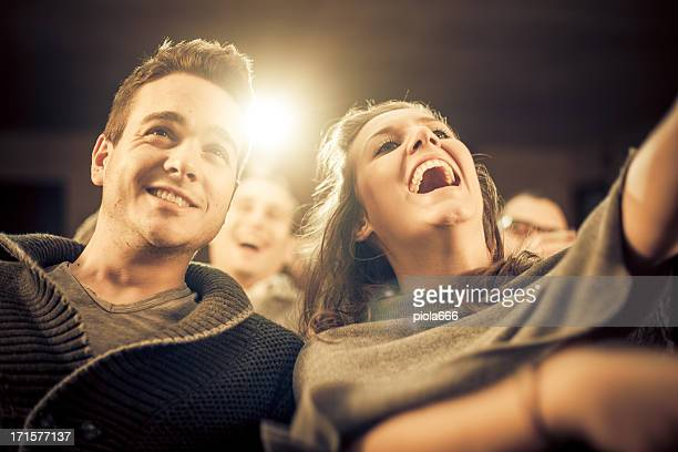Couple laughing at the cinema, watching comic movie