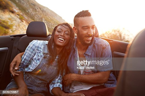 Couple laughing in the backseat of car