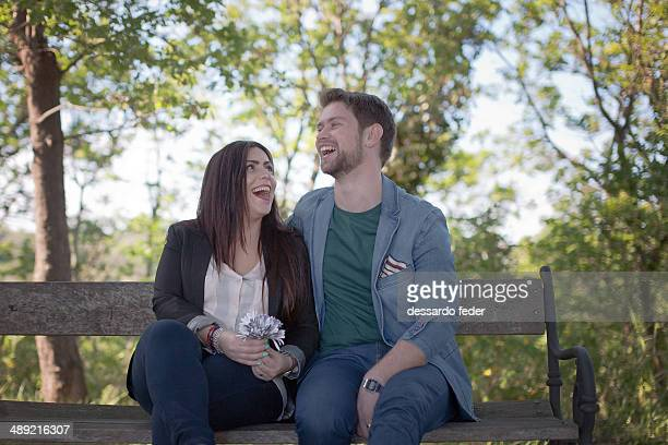 Couple laughing on the bench in park