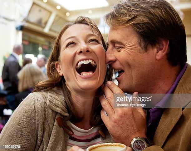 Paar Lachen bei einer Tasse Kaffee.