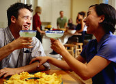 Couple Laughing Over Margaritas at a Party