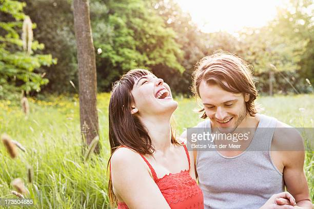 Couple laughing, sitting outdoors in grass.