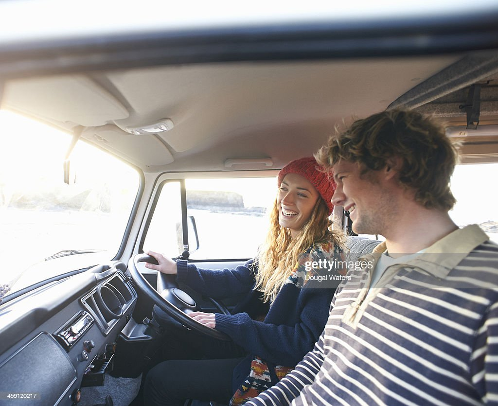 Couple laughing together in camper van. : Stock Photo